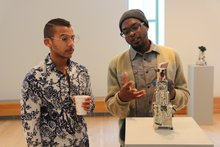 Alex Anderson '13, MFA Candidate at University of California speaking with List Gallery exhibition artist, Kevin Snipes.