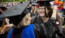 graduate hugging faculty member