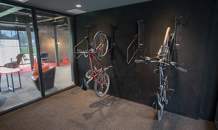 Bicycles hang from the wall on the inside of the building