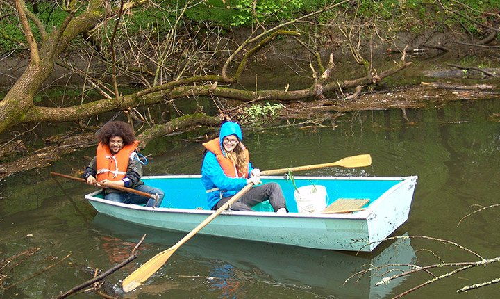 two students in row boat on crum creek
