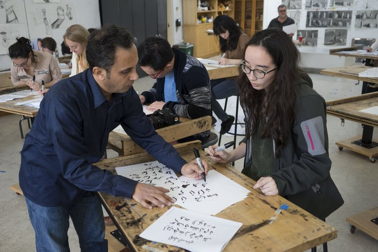 Student receiving aid with her calligraphy stroke