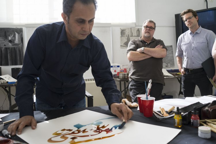 Faculty watch as Khaled al-Saai provides calligraphy demo