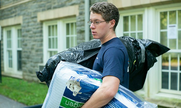 Student with hands full on move-in day