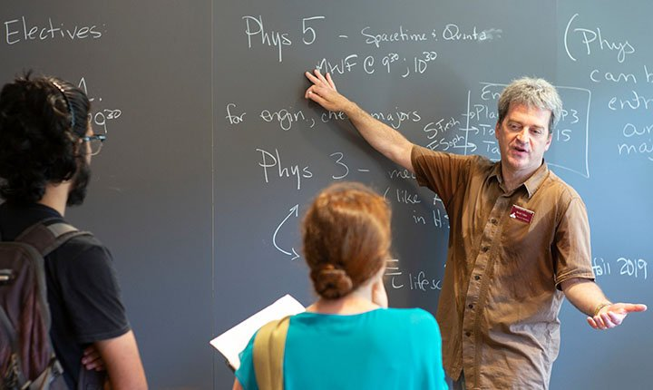 Professor points to blackboard during advising