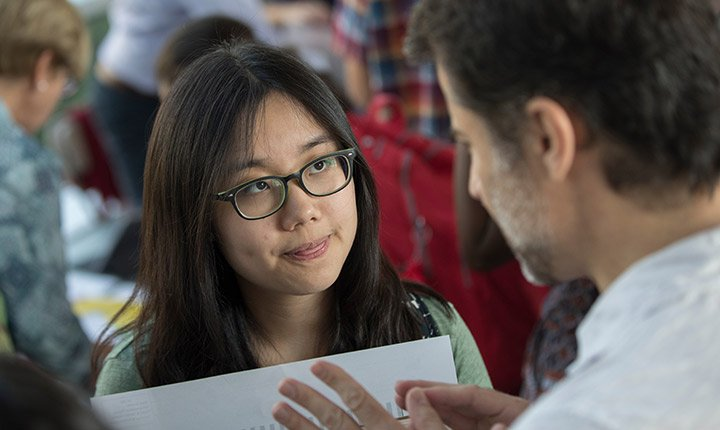 A student leans in to listen to a professor speak to her during the academic advising fair