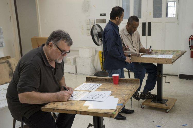 Professor Brian Meunier practices calligraphy