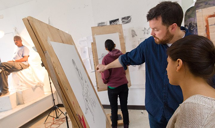 An instructor advises a student on her drawing