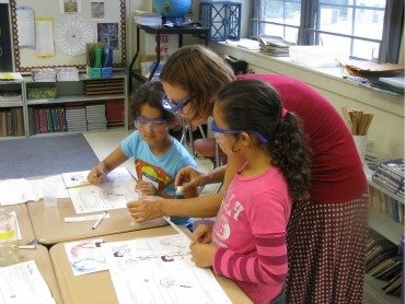 Professor Yatsunyk works with third-graders who seem fascinated by what she is doing