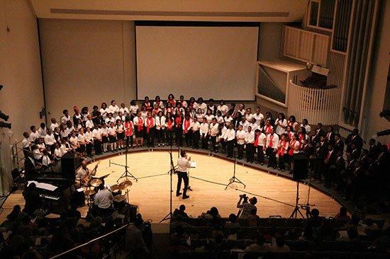 children in an auditorium being lead in song