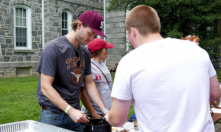 A man serves another man chili