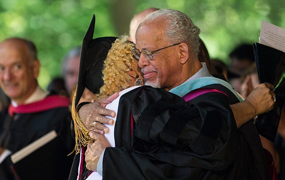Honorary degree recipient Vaneese Thomas '74 and Maurice Eldridge '61 embrace on stage at Commencement 2014