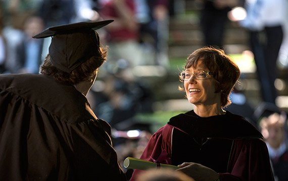 President Rebecca Chopp hands a diploma to a graduating student