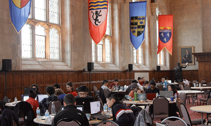 Students working on computers in the wood-paneled Thomas Great Hall