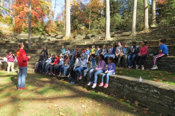 Elementary school students sit in the ampitheater with Swarthmore students from Educational Policy