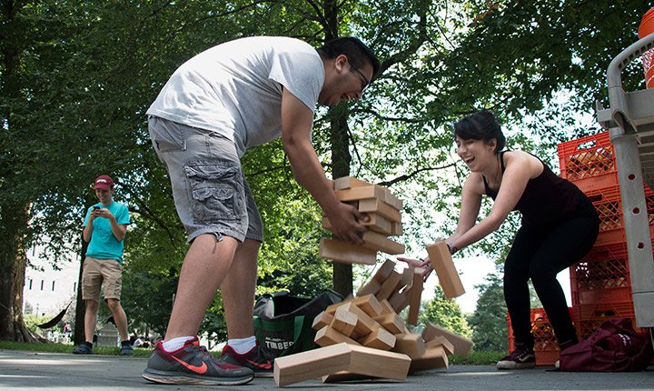 Students try to catch the pieces of a giant Jenga game as it collapses