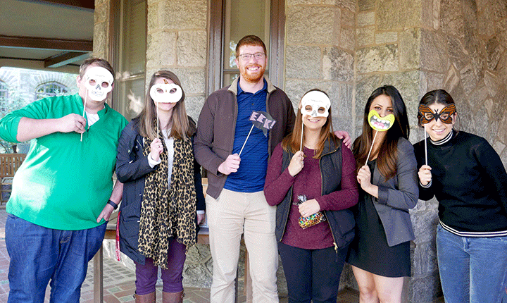 Students pose for a photo holding up their homemade halloween masks