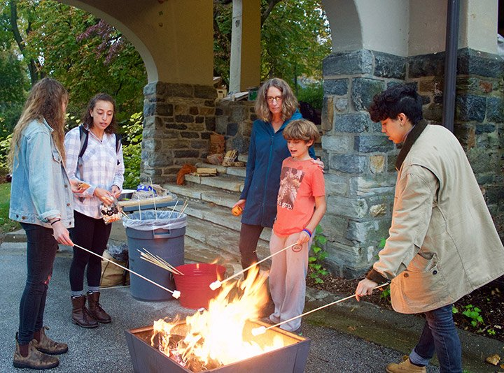Students and community members make s'mores over a fire