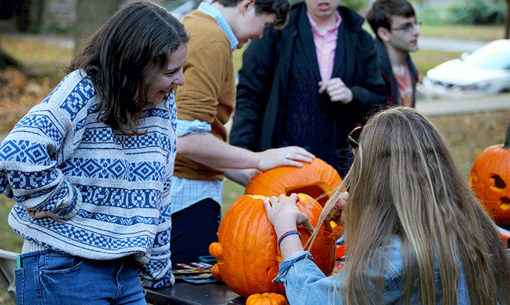 A student carves a pumpkin while another student looks on