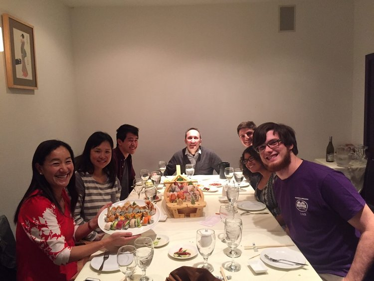 2017 graduating students and professors sitting at a dinner table.