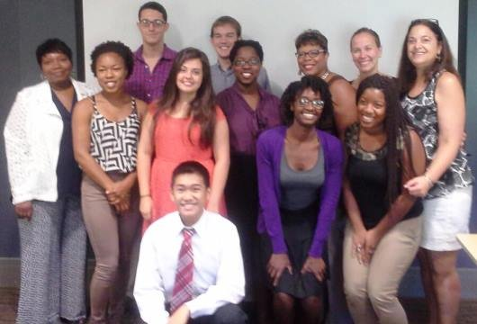 Group of students pose with community partners, staff of the Lang Center, and a professor in front of a white screen