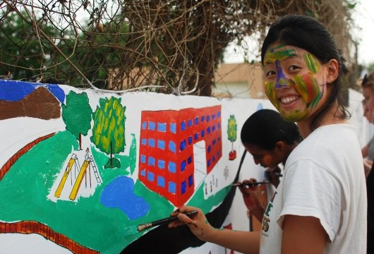 Student smiling while painting a mural in bright colors