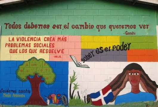 A brightly colored mural that says in Spanish, Be the Change You Wish to See in the World by Gandhi