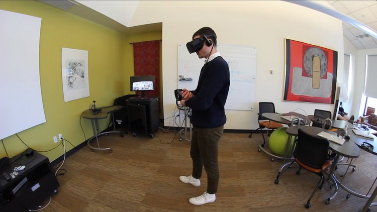 Student using Oculus VR headset and controls in the Language Center