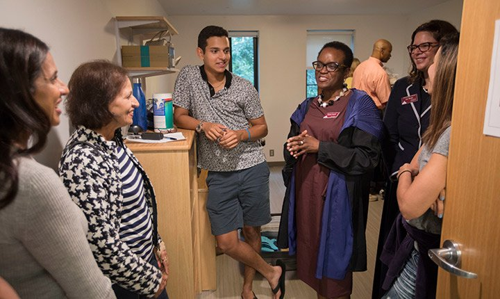 President Valerie Smith talks to a student and his family in his dorm room on move in day