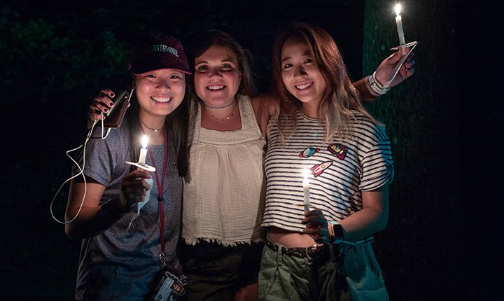 Three students hold candles facing camera