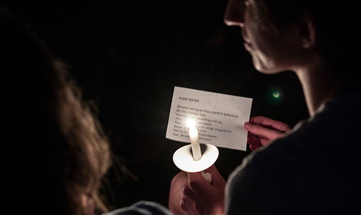 Student holds candle and copy of alma mater.