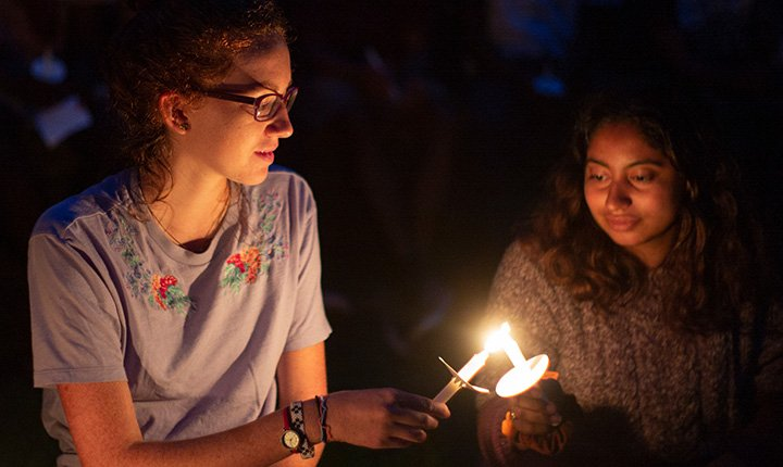 One student transfers flame to another student's candle