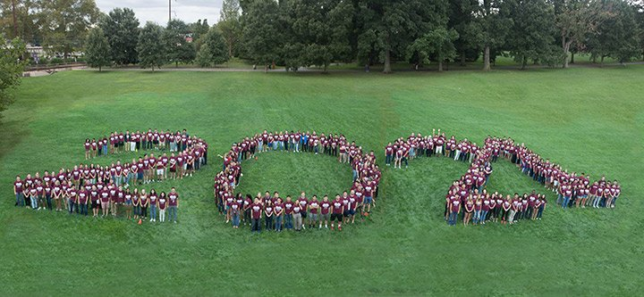Students in the Class of 2021 stand in a field in the formation of their class year