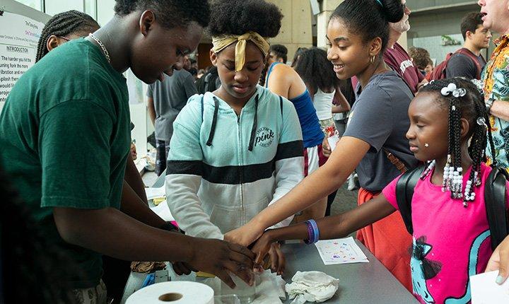 Children hold jar at science fair