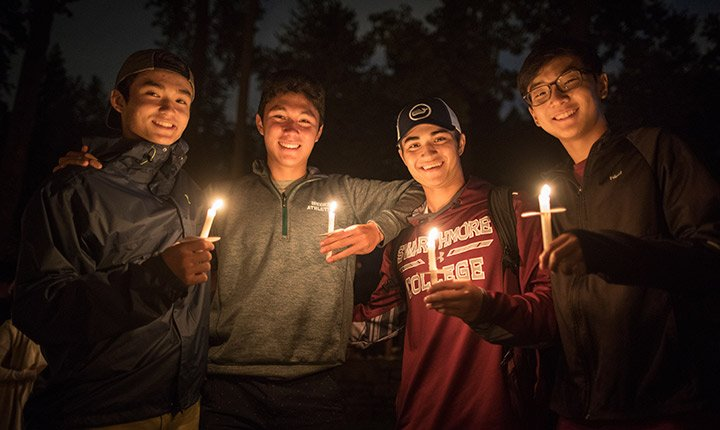 Four students post together holding lit candles