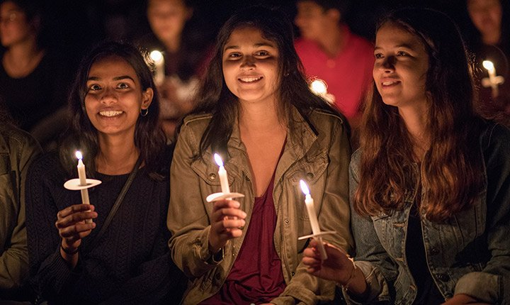 Three students sit together holding lit candles