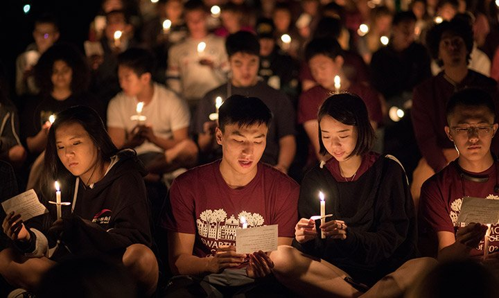 Two students lit by candle light look down at a piece of paper together