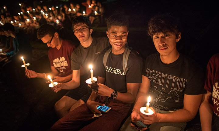 One student stares at the camera as he sits with three friends holding candles