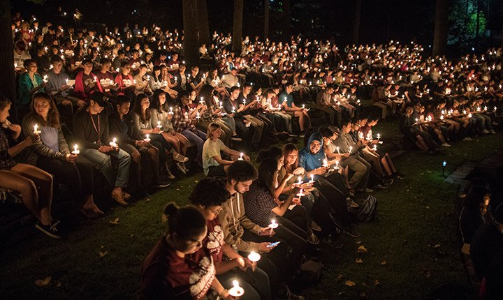 Several rows of people holding candles light up the night in the Scott Amphitheater