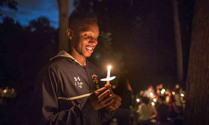 A student looks down and smiles at the candle he is holding