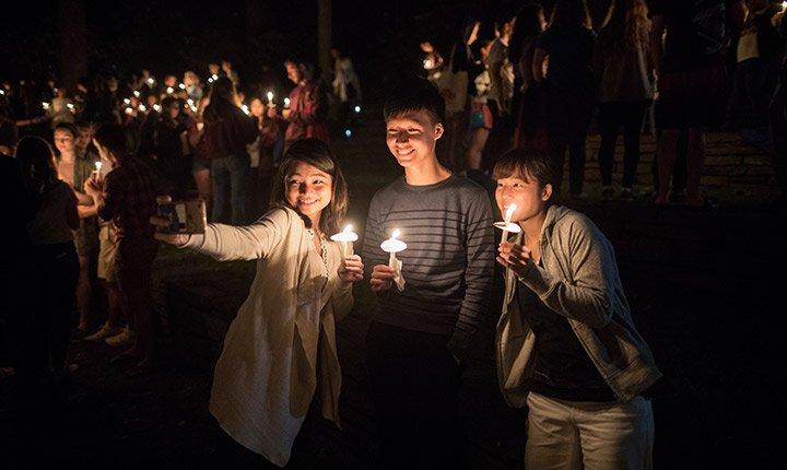 Three students take a selfie together while holding candles outside at night