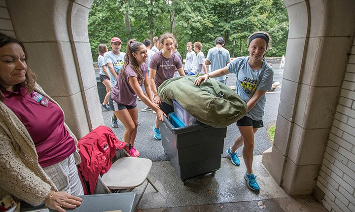 Students help carry bags of a new student on move in day