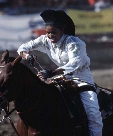A female participates in a barrel racing event in a California rodeo.