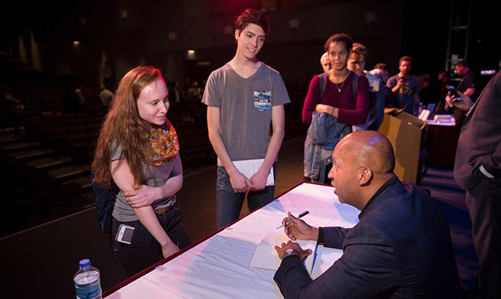 Bryan Stevenson signs a student's book following his lecture