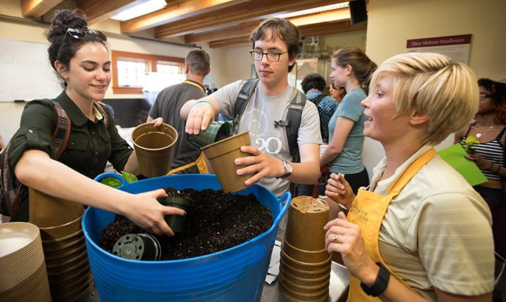 Student shovel dirt into planters at the annual plant giveaway