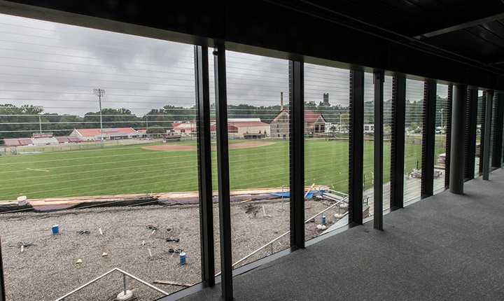 A view from the inside looking out windows onto the baseball field