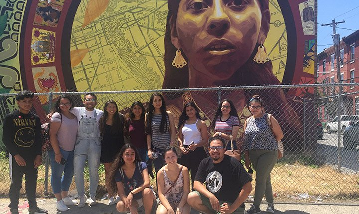 Edwin Mayorga and a group of students in front of a mural in South Philadelphia