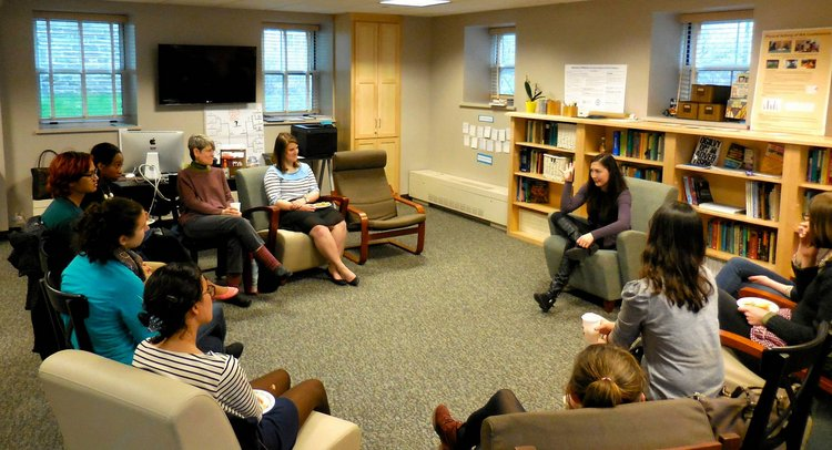 A group of students and faculty sit in an semi-circle of chairs around Maya Schenwar '05