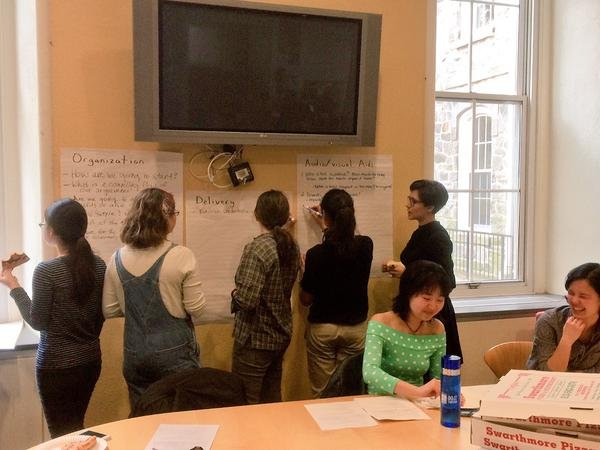 Five students stand behind a table in Shane Lounge, writing on giant sticky notes as two students sit laughing, bottom right
