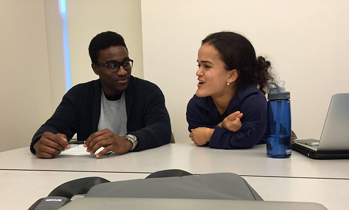 Photo of a WA sitting and talking with another student during the Fall 2015 International Write-In