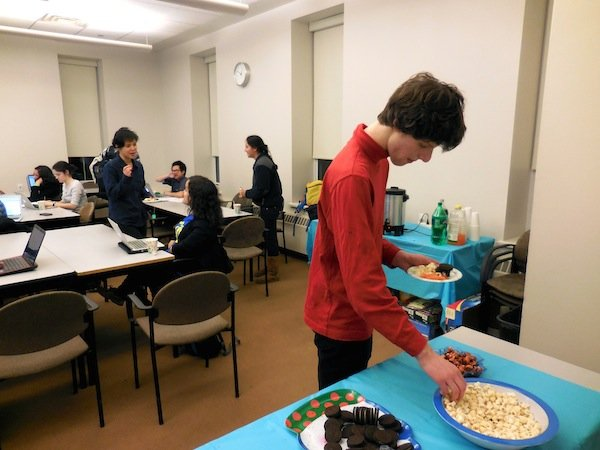 A male student in a red turtleneck reaches into a bowl of chips sitting on a blue tablecloth. A group of students type on their laptops at tables in the background.